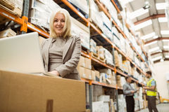 Smiling warehouse manager working on laptop Royalty Free Stock Photo