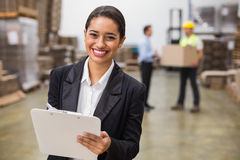 Smiling warehouse manager writing on clipboard Royalty Free Stock Photos