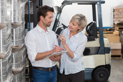 Smiling warehouse managers working on clipboard Royalty Free Stock Photography