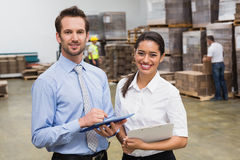 Smiling warehouse managers working together Stock Images