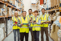 Smiling warehouse team looking at camera Stock Photography