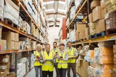 Smiling warehouse team looking at camera stock image