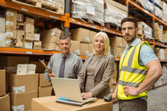 Smiling warehouse team working together on laptop Royalty Free Stock Photography