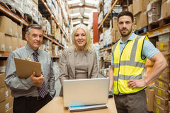 Smiling warehouse team working together on laptop Stock Photography