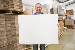 Smiling warehouse worker holding large white poster Stock Photography