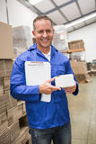 Smiling warehouse worker holding small box and clipboard Royalty Free Stock Photography