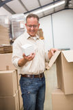 Smiling warehouse worker holding small box Stock Image