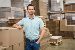 Smiling warehouse worker leaning against boxes Royalty Free Stock Photo