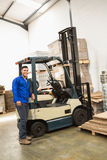 Smiling warehouse worker leaning against forklift Royalty Free Stock Photo