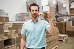 Smiling warehouse worker showing a small box Royalty Free Stock Images