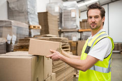 Smiling warehouse worker taking a box Stock Images