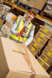 Smiling warehouse workers preparing a shipment Stock Image
