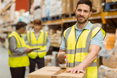 Smiling warehouse workers preparing a shipment. In a large warehouse Stock Photo