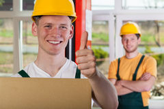 Smiling warehouseman showing thumbs up sign. Smiling warehouseman in hardhat showing thumbs up sign Stock Images