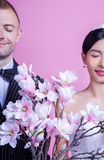 Smiling wedding couple with artificial flowers standing with eyes closed against pink background Royalty Free Stock Photo