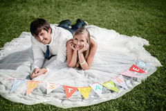 Smiling wedding couple lying on the grass Stock Photos