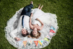 Smiling wedding couple lying on the grass Royalty Free Stock Photo