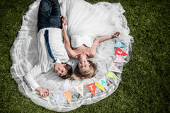 Smiling wedding couple lying on the grass Stock Images