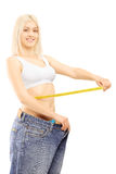 Smiling weightloss woman in old pairs of jeans measuring her wai Royalty Free Stock Image