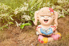 Smiling welcome girl clay doll sitting on green grass background Stock Photos