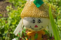 Smiling welcome a girl, a doll made of cloth, decoration in the garden. The mascot of the garden Royalty Free Stock Photography