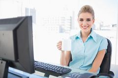 Smiling well dressed businesswoman holding coffee Stock Images