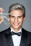 Smiling well dressed gentleman in facial mask on gray background. Royalty Free Stock Images