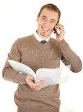 Smiling well-dressed man with documents and phone. Young well-dressed man in formalwear is talking by phone and holding a open white file with documents Stock Image