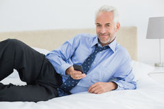 Smiling well dressed man text messaging in bed Royalty Free Stock Photography