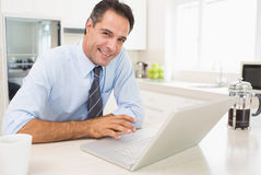 Smiling well dressed man using laptop in kitchen Stock Images