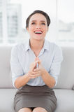 Smiling well dressed woman applauding while looking up Stock Images