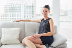 Smiling well dressed woman sitting on sofa at home Royalty Free Stock Photos