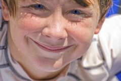 Smiling Wet Face Boy. A young smiling teen who has spent a day on the lake skiing and swimming royalty free stock photography