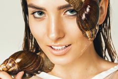 Smiling wet woman with snails on face Royalty Free Stock Images