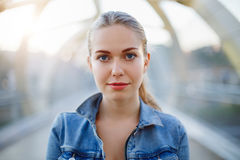 Smiling white Caucasian girl woman with pony tail, wearing jeans jacket outside in evening night city street bridge. Closeup portrait of beautiful pensive blonde stock photos