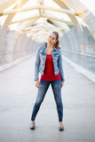 smiling white Caucasian girl woman with pony tail, wearing jeans jacket outside in evening night city street bridge Stock Photo