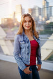 Smiling white Caucasian girl woman with pony tail, wearing jeans jacket outside in evening night city street bridge Royalty Free Stock Image