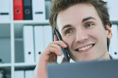 Smiling white collar talking to customer on mobile phone in office at workplace by laptop. Stock Photography