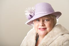 Smiling white-haired woman in hat and fur Royalty Free Stock Photos