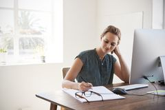 Smiling white woman working in an office making notes Royalty Free Stock Images