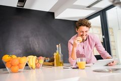 Smiling white young man, looking at the tablet, having breakfast. stock photo