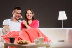 Smiling wife feeding happy husband with banana. Royalty Free Stock Photography