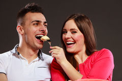 Smiling wife feeding happy husband with banana. Royalty Free Stock Photography