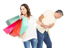 Smiling wife holding shopping bags with husband pulling her hand Stock Photography