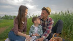 Smiling wife with husband and little boy pour milk into glasses and drink during family picnic and enjoy outdoor. Recreation in green field close up stock footage