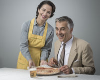Smiling wife serving dinner Royalty Free Stock Photo