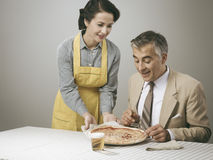 Smiling wife serving dinner Royalty Free Stock Photography