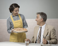 Smiling wife serving dinner Stock Image