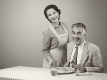 Smiling wife serving dinner Royalty Free Stock Image