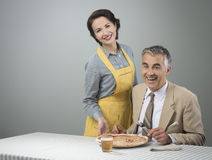 Smiling wife serving dinner Royalty Free Stock Photos